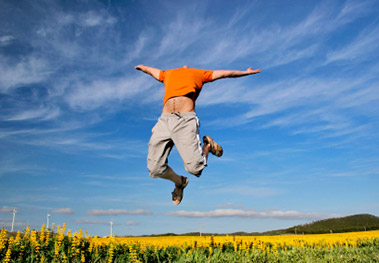 Man jumping in energeitc manner in field