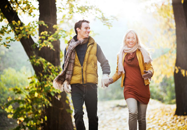 Young couple taking a leisurely walk through woods